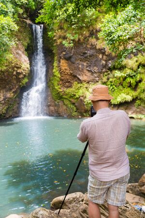 Photographer taking photo of The Chamouze waterfall. Mauritius island photo