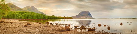 Amazing view of Le Morne Brabant at sunset. Mangroves and stones on the foreground. Mauritius island. Panorama