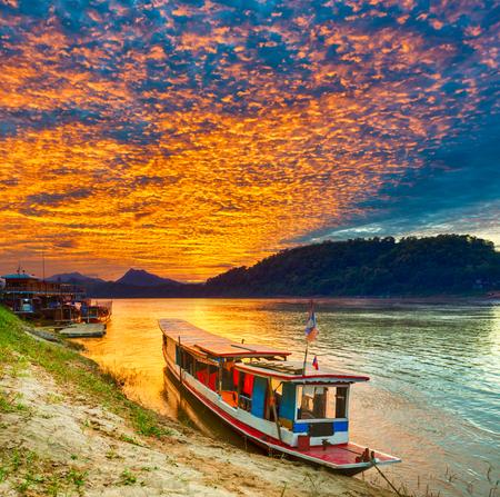 Touristic boat at sunset time. Beautiful landscape. Luang Prabang. Laos. Stock Photo