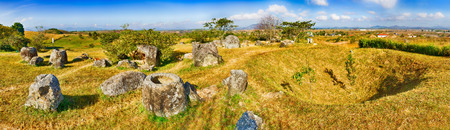 Archaeological landscape The Plain of jars. Bomb crater and jars. Laos. Panorama