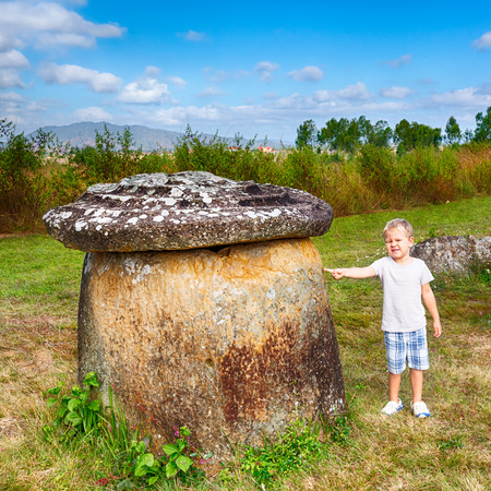 Child pointing to the jar. Archaeological landscape The Plain of jars. Laos Stock Photo