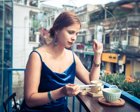 Beautiful woman enjoying tea and dessert on cafe terrace in Dalat, Vietnam.