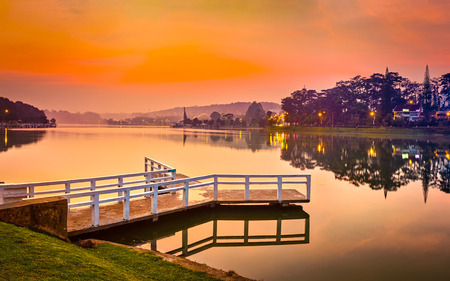 Amazing view of sunrise over Xuan Huong Lake, Dalat, Vietnam. Pier on the foreground. Landscape photo. Panorama
