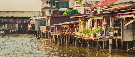 Scenic view of Bangkok riverside, Thailand. Slums on stilts on the foreground. Panorama Stock Photo