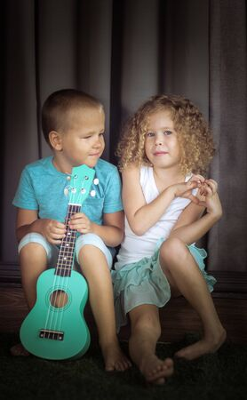 Portrait of a cute kids sitting ouddoor with ukulele 写真素材