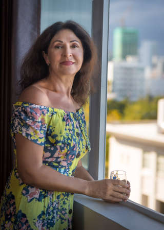 Indoor portrait of a beautiful smiling senior woman next to window holding glass of water