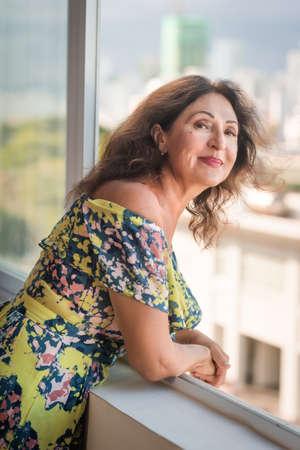 Indoor portrait of a beautiful smiling senior woman next to window 免版税图像