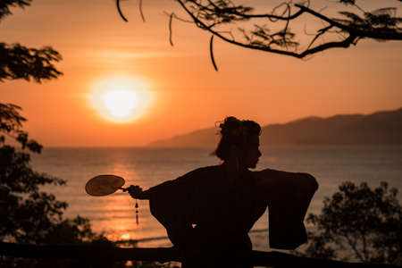 Silhouette of Japanese Geisha in kimono with fan at sunrise