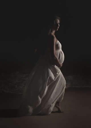 Outdoor portrait of a beautiful pregnant woman at night