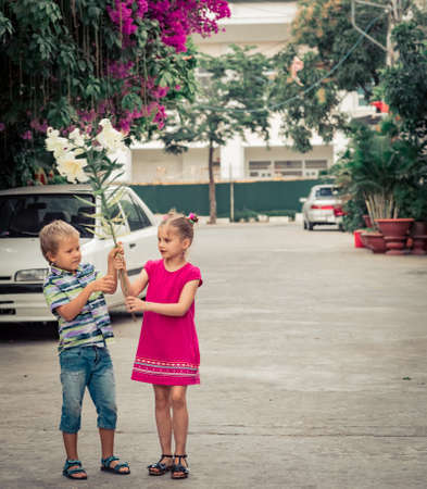 Kids walking by the street with flower