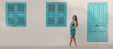 Outdoor portrait of a beautiful pregnant woman. Panorama