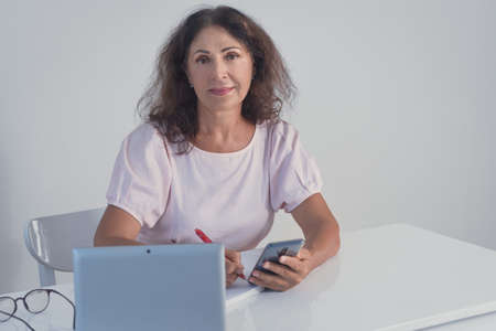 Indoor portrait of a beautiful smiling senior woman working at home