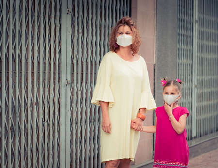 Woman and daughter wearing facial disposable mask to avoid viral infection. Coronavirus protection 免版税图像