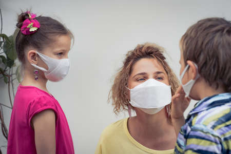 Family wearing facial disposable mask to avoid viral infection. Coronavirus protection 免版税图像