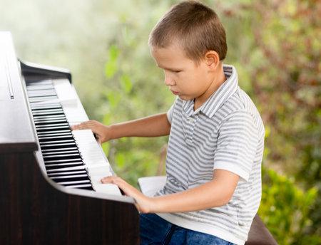 Cute lttle boy playing piano outdoor Zdjęcie Seryjne