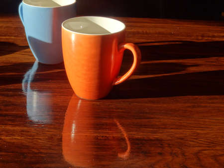side lighting: Close up of breakfast cups and shadows on wood grain table.
