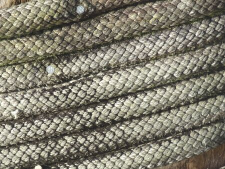 coiled rope: Close up of coiled rope on wharf bollard.