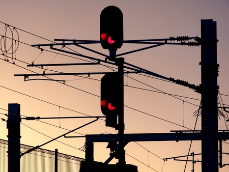 pink skies: Silhouettes of traffic lights and railway overhead lines