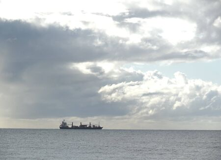 cloud formations: Distant view of freighter on horizons with cloud formations Stock Photo