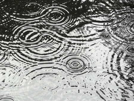 Rain ripples on pond making circular patterns Stock Photo