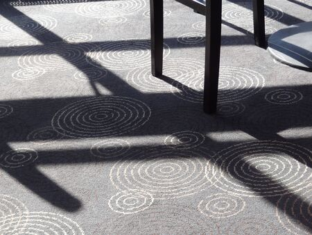floor covering: Sunlight and shadow on decorative carpet and table legs Stock Photo