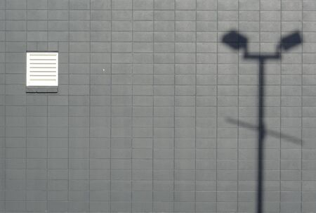 lamp post: Gray brick wall with lamp post shadow composition