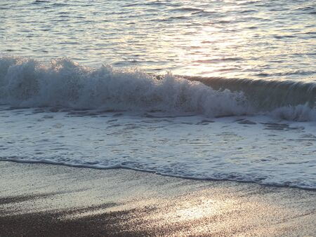 Wave breaking on deserted beach at sunset