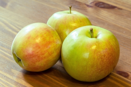 three apples laying on the wooden table photo