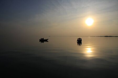 two boats in tranquil water, sunset time photo