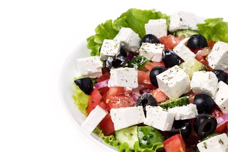 part of plate with greek salad isolated on white background photo