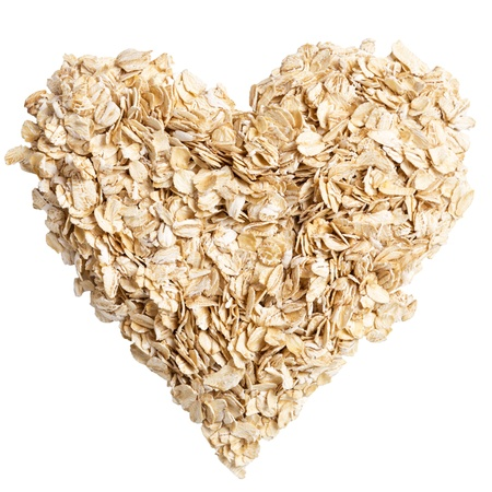 oat plant: heap of oat flakes in a shape of heart shot from above Stock Photo