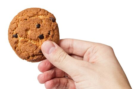 cookie with chocolate pieces in hand, isolated photo