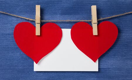 Two paper hearts and card hanging on a rope, valentines day theme Stock Photo - 17038820