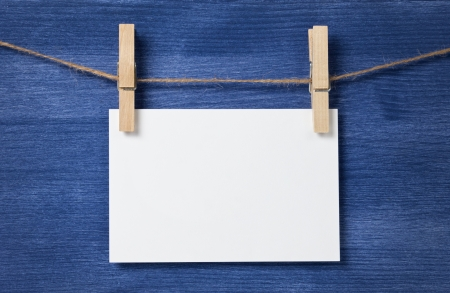 white blank paper card hanging over wood background, template photo