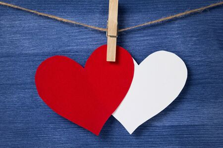 Two paper hearts hanging on a rope, valentines day theme Stock Photo - 17038844