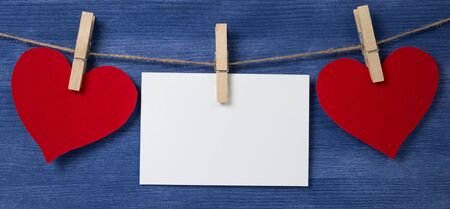 Two paper hearts and card hanging on a rope, valentines day theme Stock Photo - 17030344