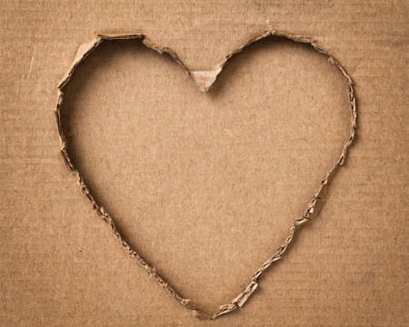 hole in a shape of heart on cardboard, valentines theme Stock Photo