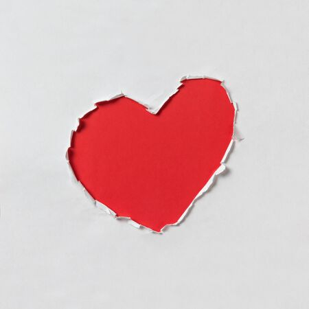 hole in shape of a heart, white and red paper photo