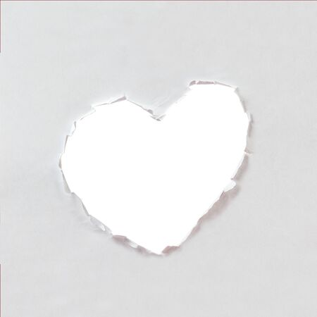 hole in shape of a heart, white paper photo