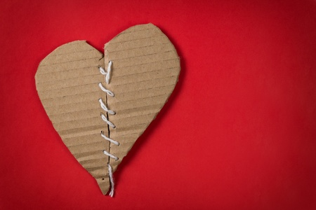 broken relationship: fixed brocken heart, isolated on red paper