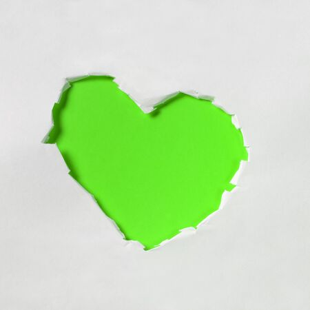 hole in shape of a heart, white and green paper photo