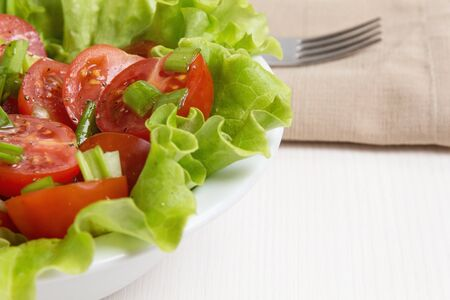 fresh light salad with cherry tomatoes and chives, on white wood table photo