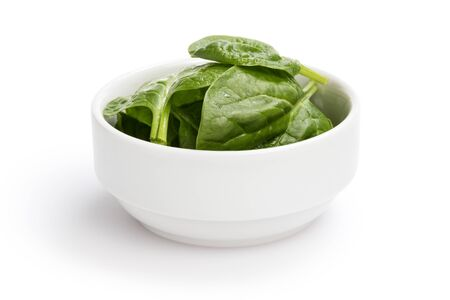 fresh spinach leaves in bowl, isolated on white photo