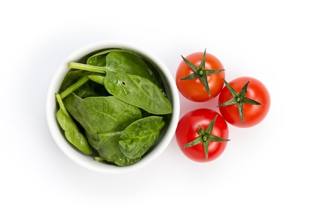 fresh spinach leaves in bowl and tomatoes, isolated on white photo