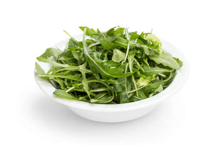 fresh rucola leaves in a bowl, isolated on white photo