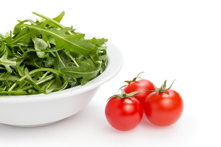 fresh rucola leaves in a bowl and tomatoes, isolated on white photo
