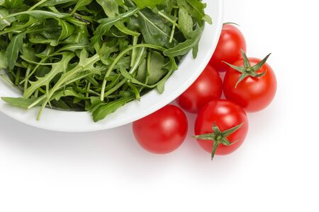fresh rucola leaves in a bowl and tomatoes, isolated on white Stock Photo - 18167189