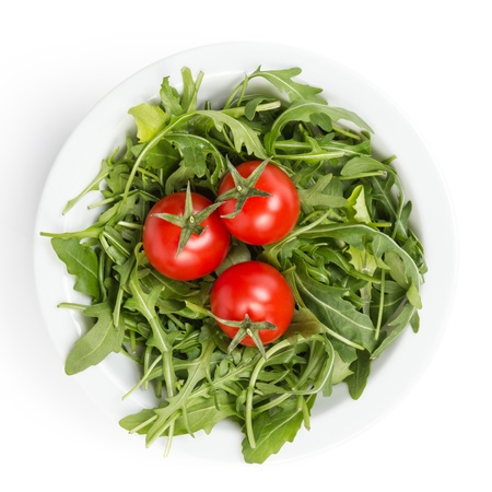 fresh rucola leaves in a bowl with tomatoes, isolated on white photo