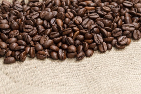 heap of coffee beans on burlap, background photo