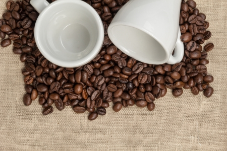 heap of coffee beans on burlap with two cups, cafe theme photo